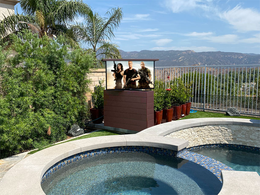 Outdoor TV Lift in composite decking next to Pool and spa