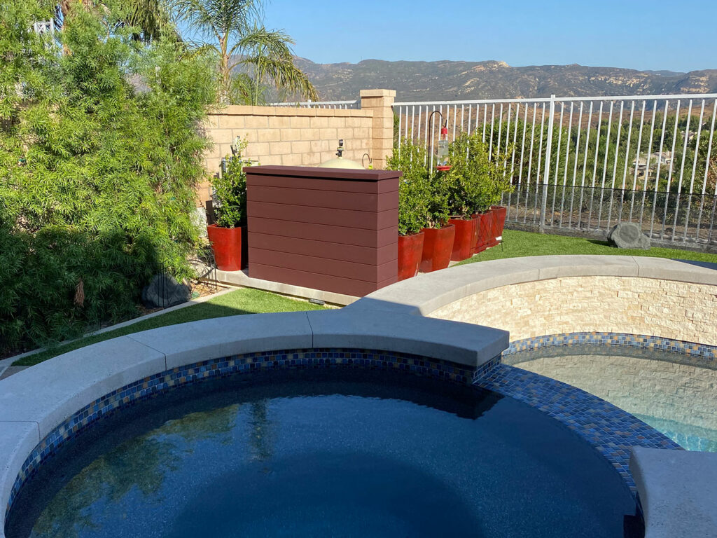 Composite decking outdoor TV lift installed next to pool and spa