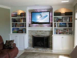 Custom built-in wall unit surrounding fireplace in white