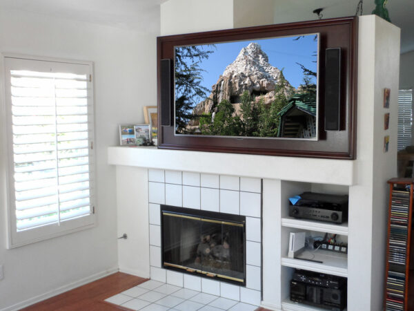 Custom back wall above fireplace for a large flat panel TV and two on-wall speakers