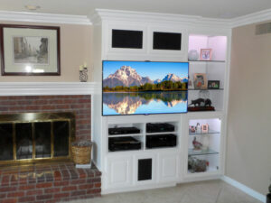 White built-in wall unit modified for flat panel TV, electronic storage, and lighted display space.