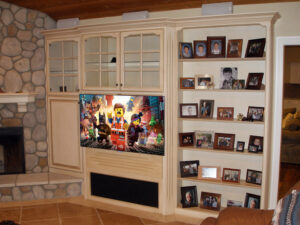 This built-in wall unit was upgraded with a structural TV back wall, heavy-duty, double-arm, pull-out bracket, and a decorative frame out panel to match the styling of the furniture.