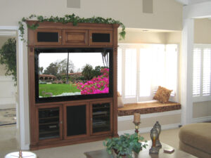 Beautiful built-in home theater armoire next to window seat