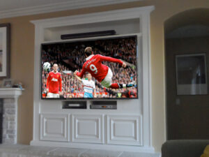 This white built-in wall unit was upgraded to acommodate a modern flat panel TV and Sonos sound bar.