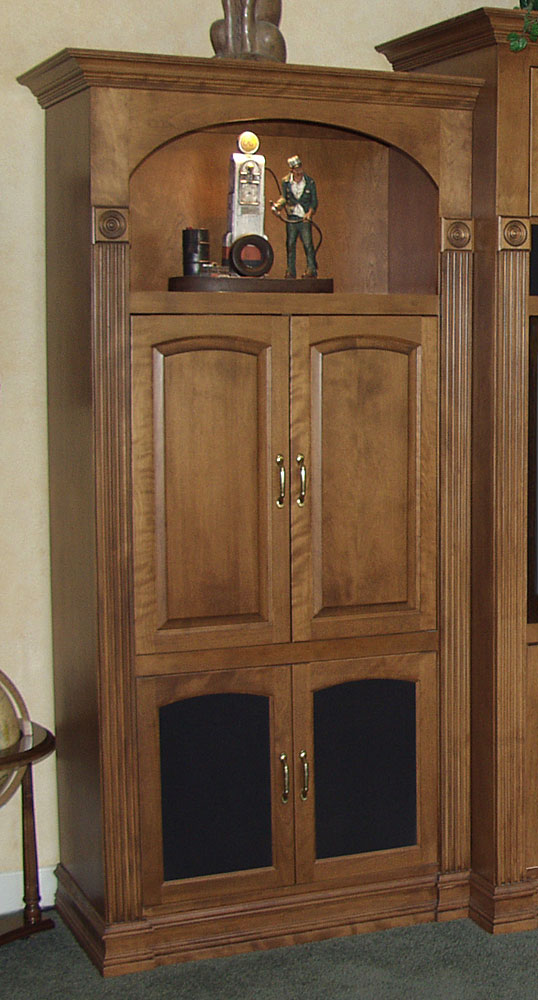 A close-up view of the decorate side storage cabinets with lighted display space, raised panel arched doors, and speaker cloth panels.