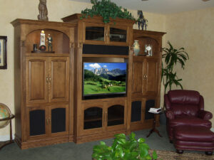 Traditional wall unit with decorative arches, lights, and a flat panel TV mounted to a pull-out articulating wall bracket.