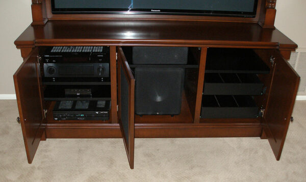 The interior of the furniture organized electronics, a center speaker, a subwoofer, and featured a pair of media drawers